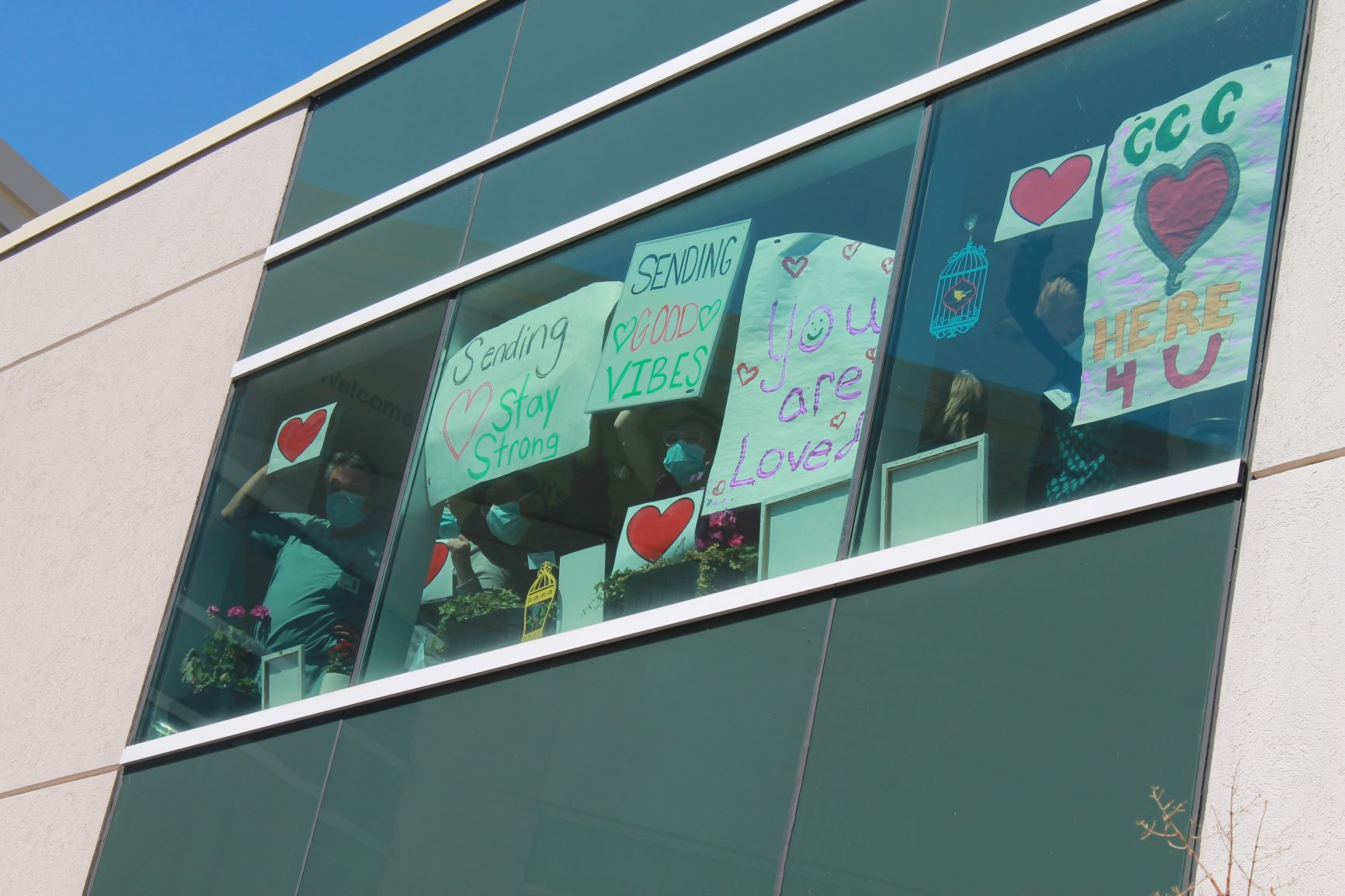 Residents inside SJV building holding signs with positive messages in the windows