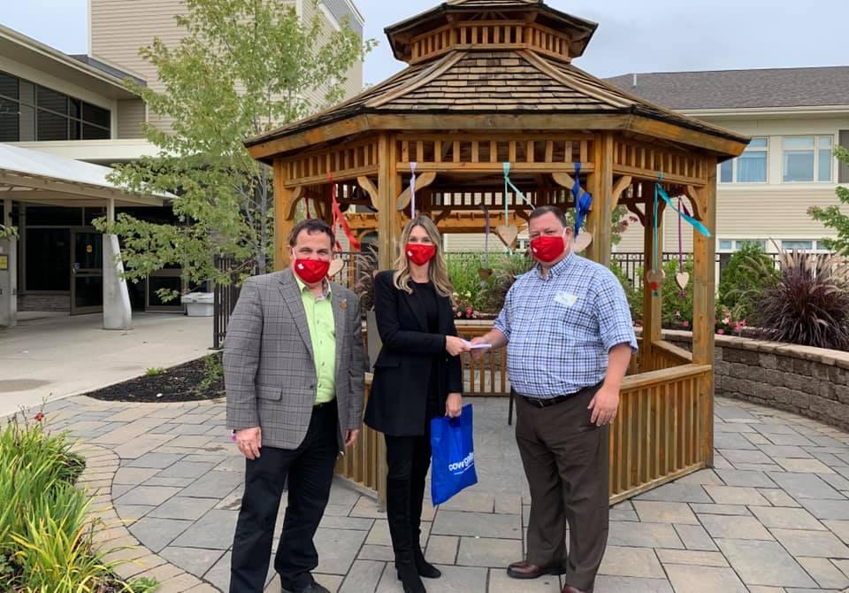 Marc Serre, Alicia Wood and Ray Ingriselli outside in front of a gazebo for the cheque presentation