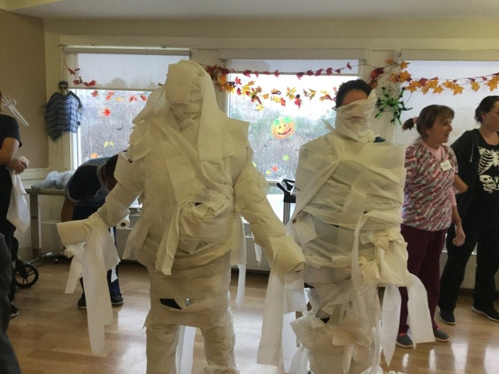 Two people wrapped in toilet paper to look like mummies for Halloween
