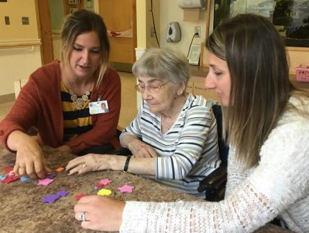 Staff help resident with a puzzle