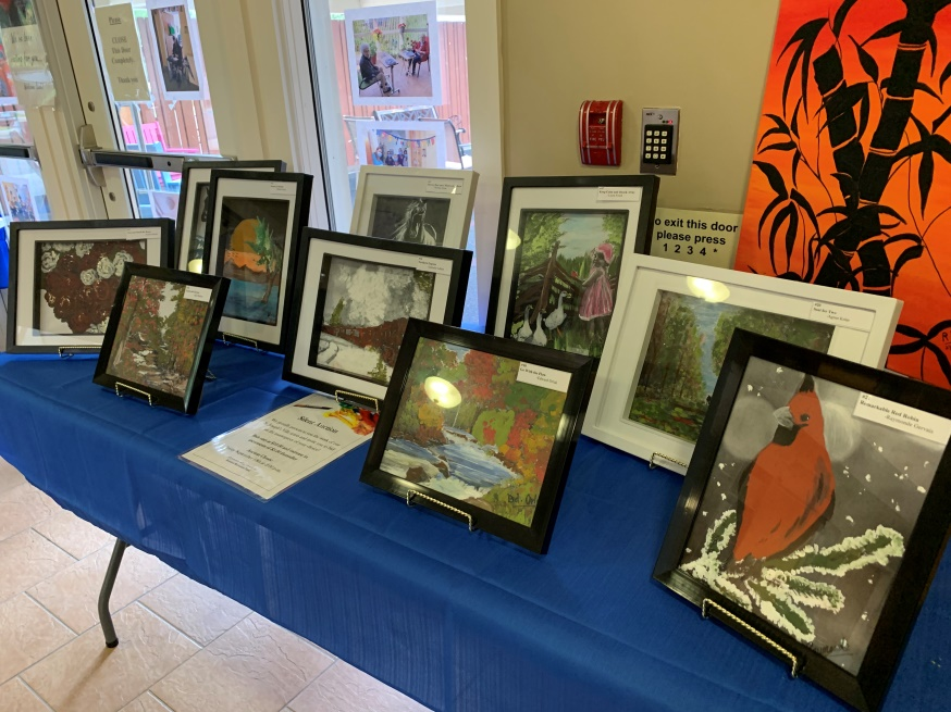 Framed artwork on display table for silent auction