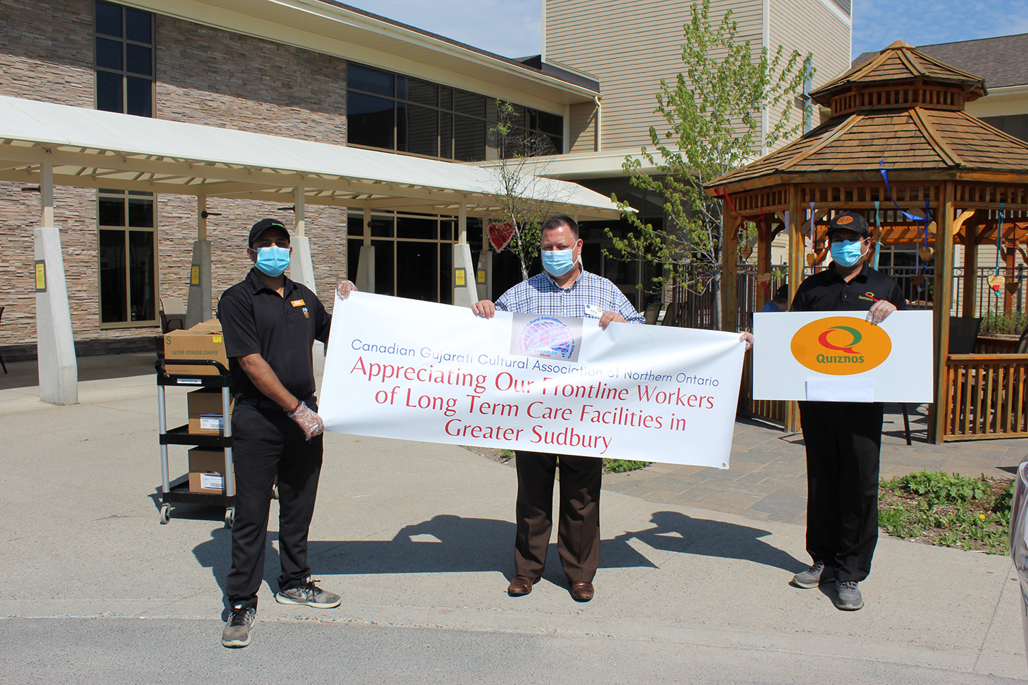 Manthan Patel and Dhiren Patel holding banner showing donation