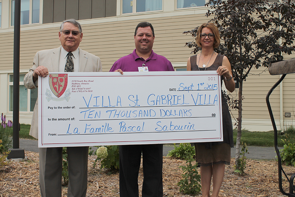 Pascal Sabourin presents a cheque to Jo-Anne Palkovits and Ray Ingriselli